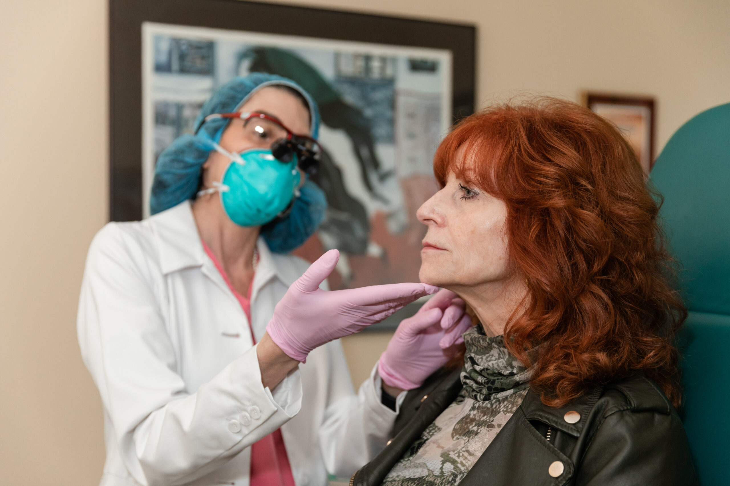 Plastic surgeon examining skin of a female patient to perform non surgical skin tightening, Princeton, NJ