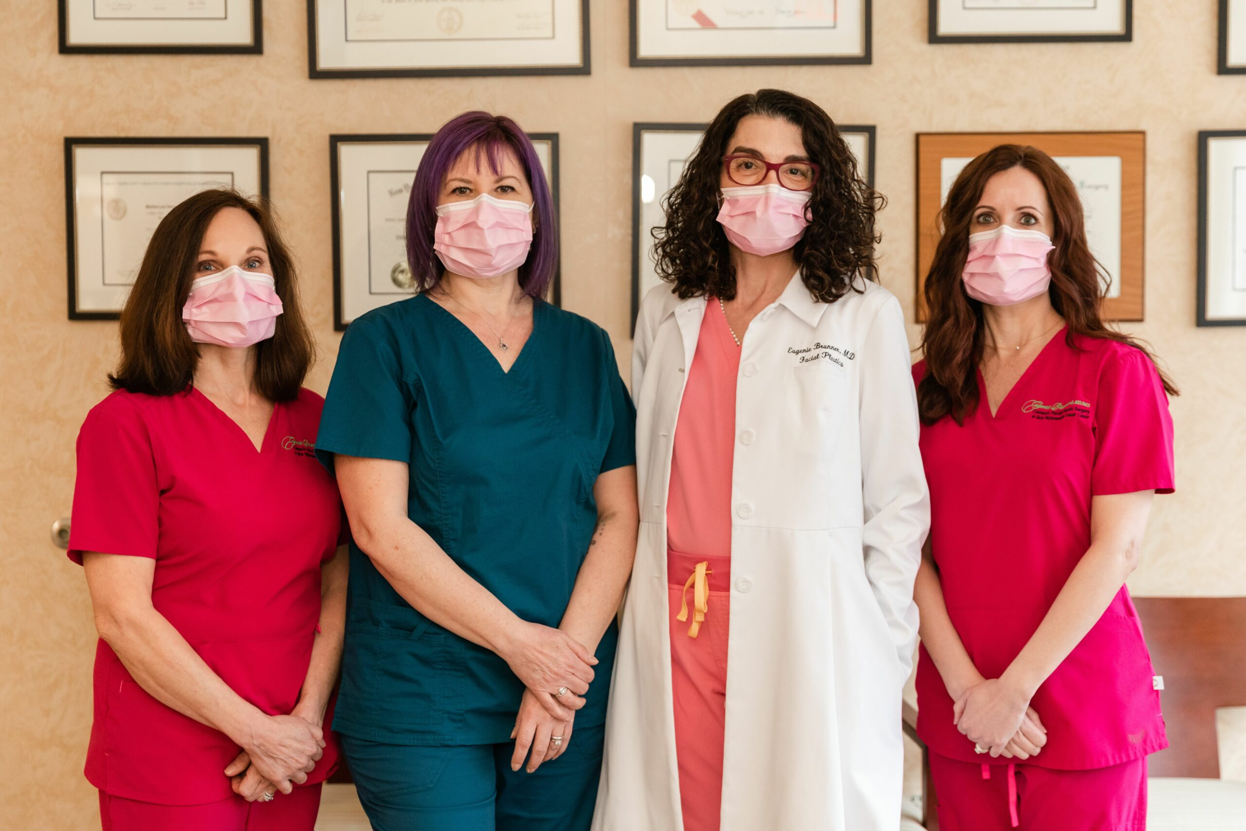 Group photo of Dr. Eugenie Brunner M.D, F.A.C.S with her staff wearing masks following covid protocols in their office, NYC.